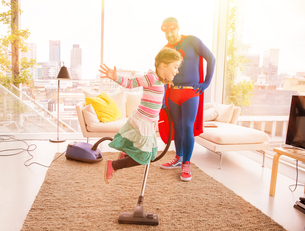 Superhero father vacuuming while daughter jumps in living roomの写真素材 [FYI02187743]