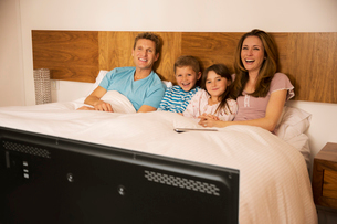 Family watching television in bedの写真素材 [FYI02187744]
