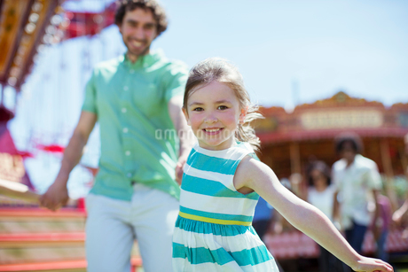 Girl pulling her father in amusement parkの写真素材 [FYI02187748]