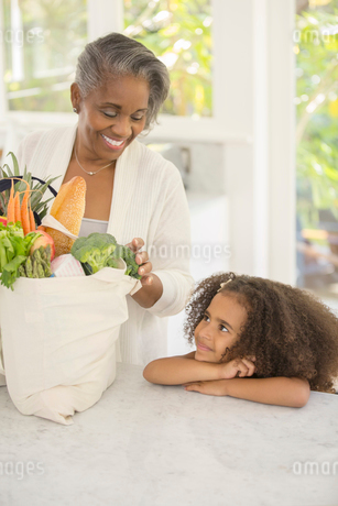 Grandmother and granddaughter unpacking groceries in kitchenの写真素材 [FYI02187751]