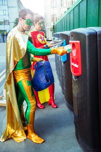 Superhero couple recycling on city sidewalkの写真素材 [FYI02187757]