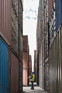 Worker standing between cargo containersの写真素材 [FYI02187765]
