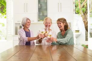 Senior women toasting wine glasses in kitchenの写真素材 [FYI02187770]
