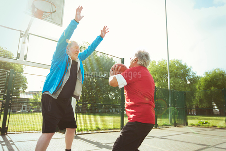 Active senior men playing basketball in sunny parkの写真素材 [FYI02187772]
