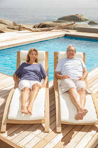 Senior couple laying on lounge chairs at poolsideの写真素材 [FYI02187781]