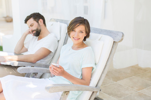 Couple relaxing in lawn chairs outdoorsの写真素材 [FYI02187803]