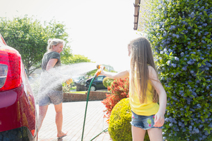 Playful daughter spraying mother with hose in sunny drivewayの写真素材 [FYI02187811]