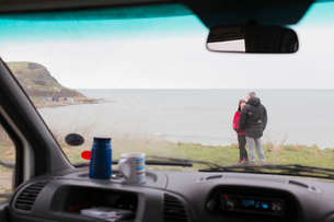 Couple talking outside motor home on cliff overlooking oceanの写真素材 [FYI02187855]