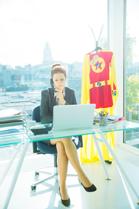 Businesswoman working at office desk with superhero costume behind herの写真素材 [FYI02187862]