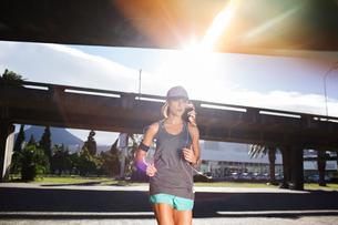 Woman running through city streetsの写真素材 [FYI02187873]