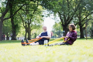 Active senior couple exercising, using resistance bands in parkの写真素材 [FYI02187892]