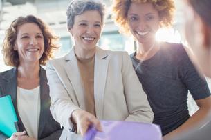 Three smiling businesswomen holding documentsの写真素材 [FYI02187906]