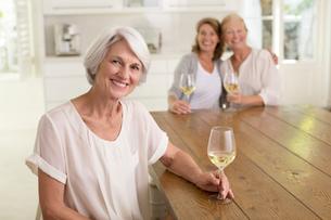 Senior women drinking white wine in kitchenの写真素材 [FYI02187915]