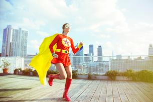 Superhero running on city rooftopの写真素材 [FYI02187921]