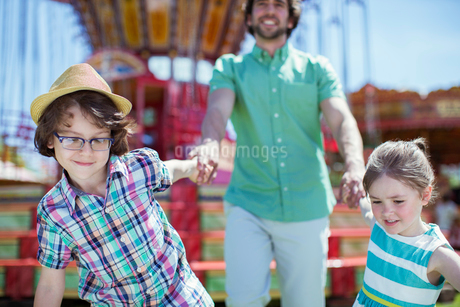 Girl and boy pulling their father in amusement parkの写真素材 [FYI02187933]