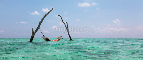 Young woman laying in hammock over tranquil blue ocean, Maldives, Indian Oceanの写真素材 [FYI02187938]