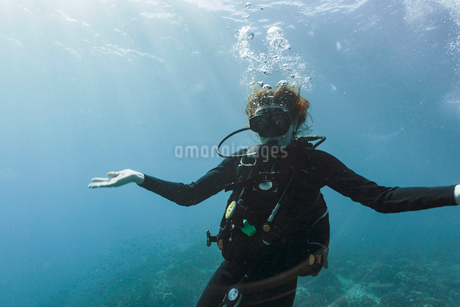 Portrait young woman scuba diving underwater with arms outstretchedの写真素材 [FYI02187939]