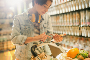 Young woman with headphones using cell phone in grocery store marketの写真素材 [FYI02187958]