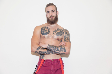 Portrait confident, cool male hipster with bare chest and tattoosの写真素材 [FYI02187959]