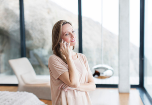 Woman talking on cell phone in modern living roomの写真素材 [FYI02187973]