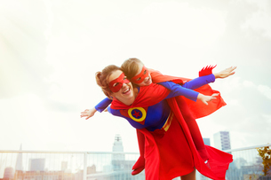 Superhero mother and daughter playing on city rooftopの写真素材 [FYI02187981]
