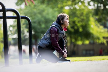Active senior female runner with headphones tying shoe in parkの写真素材 [FYI02187986]
