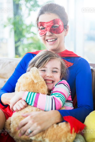 Superhero mother hugging daughter on sofaの写真素材 [FYI02187992]