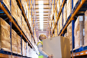 Worker carrying box in warehouseの写真素材 [FYI02188058]