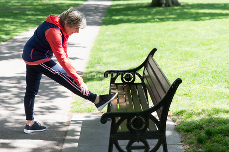Active senior woman stretching leg on park benchの写真素材 [FYI02188069]