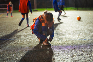 Girl soccer player tying shoe on field at nightの写真素材 [FYI02188070]