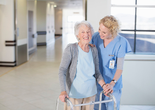Nurse helping senior patient with walker in hospital corridorの写真素材 [FYI02188072]