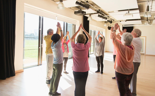Active seniors exercising, stretching arms overhead in circleの写真素材 [FYI02188074]