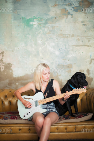 Young woman with dog playing electric guitar on sofaの写真素材 [FYI02188085]