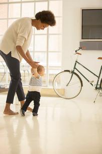 Mother helping baby boy walk in living roomの写真素材 [FYI02188106]
