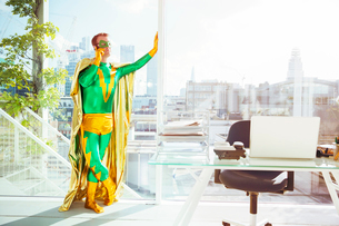 Superhero talking on cell phone in officeの写真素材 [FYI02188112]