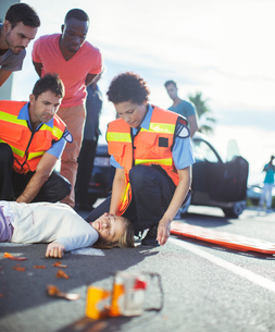 Paramedics examining injured girl on streetの写真素材 [FYI02188117]