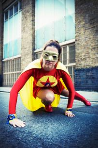 Superhero crouching on city streetの写真素材 [FYI02188125]
