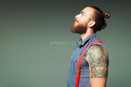 Curious hipster man with beard and shoulder tattoo looking upの写真素材 [FYI02188127]