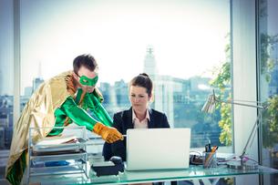 Superhero helping businesswoman working at office deskの写真素材 [FYI02188150]