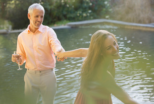 Couple holding hands by pool outdoorsの写真素材 [FYI02188159]