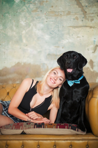 Portrait smiling, carefree young woman with black dog wearing bow tie on sofaの写真素材 [FYI02188187]