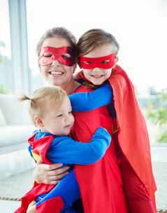 Superhero mother and children hugging in living roomの写真素材 [FYI02188215]