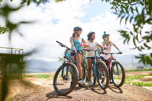 Women friends mountain biking on sunny obstacle course trailの写真素材 [FYI02188230]