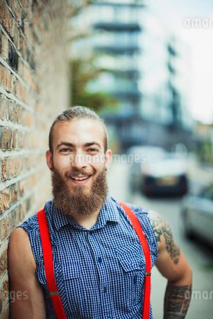 Portrait confident, smiling male hipster on urban sidewalkの写真素材 [FYI02188243]