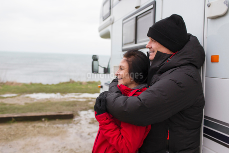 Affectionate couple in warm clothing hugging outside motor homeの写真素材 [FYI02188252]