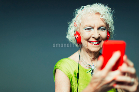 Carefree senior woman with headphones and mp3 player listening to musicの写真素材 [FYI02188263]