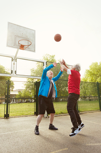 Active senior men friends playing basketball in parkの写真素材 [FYI02188270]