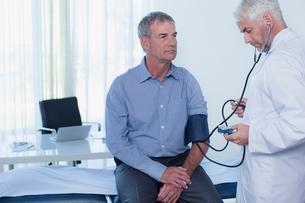 Mature doctor taking patient's blood pressure in officeの写真素材 [FYI02188278]