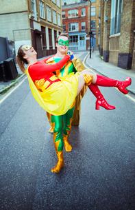 Superhero carrying wife on city streetの写真素材 [FYI02188285]