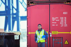 Worker smiling near cargo containerの写真素材 [FYI02188300]
